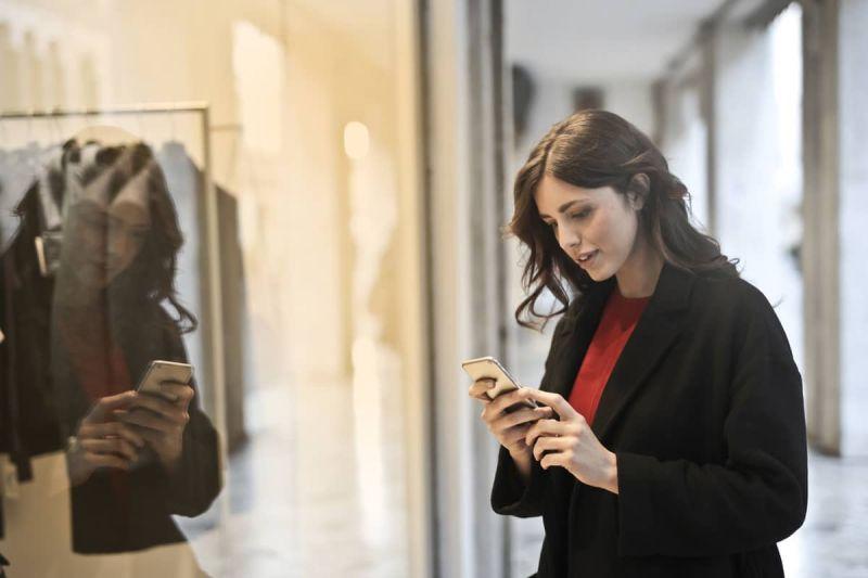 Vrouw winkelt met mobiel in haar hand.