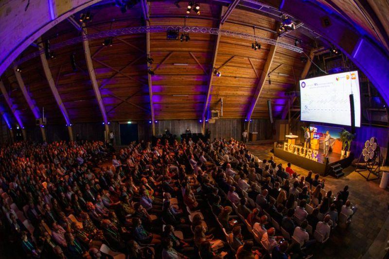 Mensen kijken in een zaal naar een presentatie