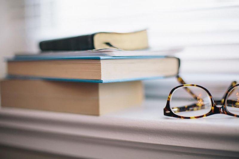 Bril en boeken op de vensterbank