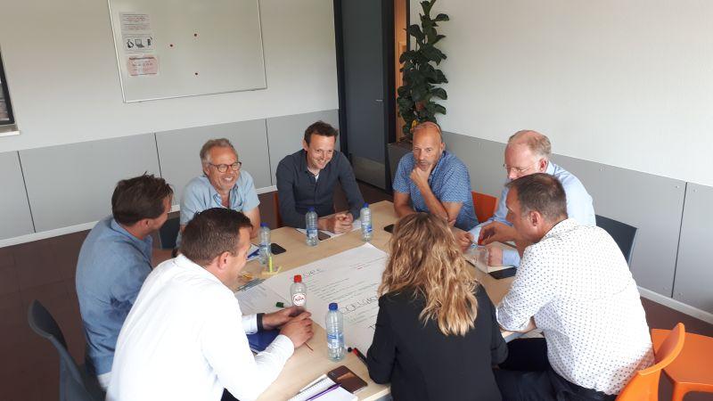 Experts zitten aan een tafel en overleggen